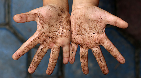 close-up of the dirt-covered palms of a young boy