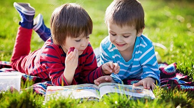 Photo of two kids reading in nature, Shutterstock