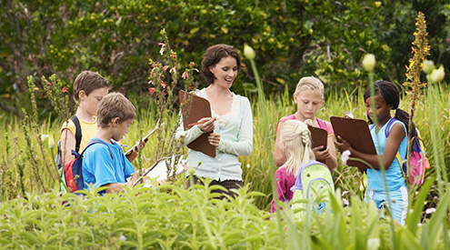 teacher with students holding clipboards in a field of grass
