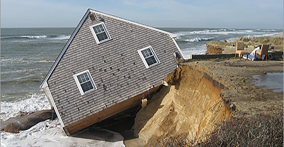 a house falling into the ocean