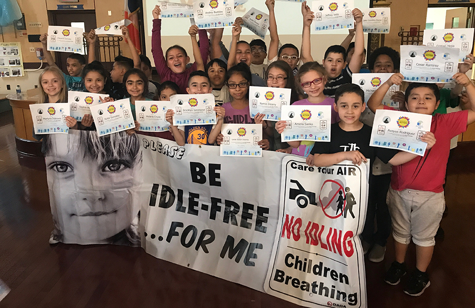 Kids holding signs to stop car idling