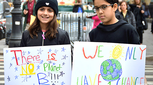 two young people holding signs