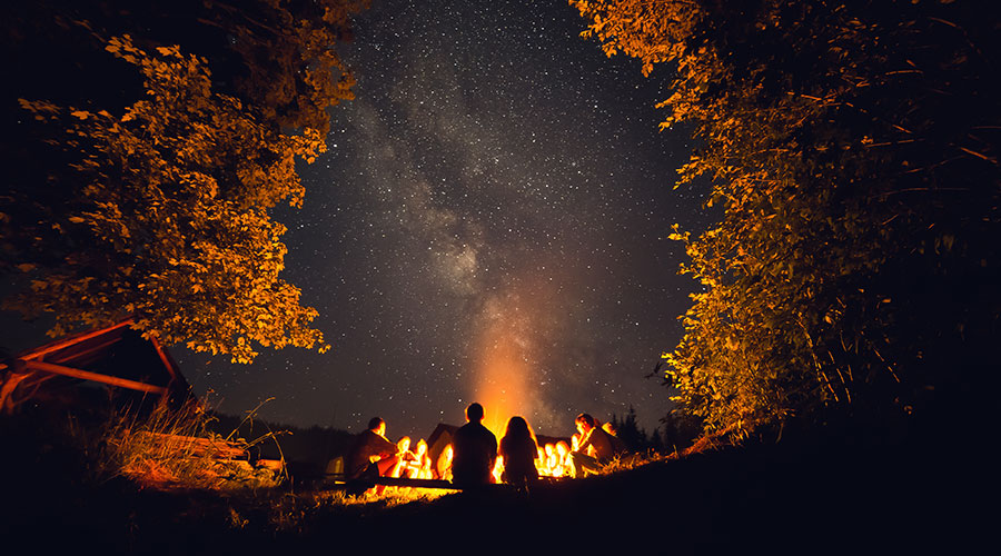 a group of people around a campfire under the stars