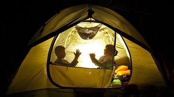 two kids camping in a tent at night