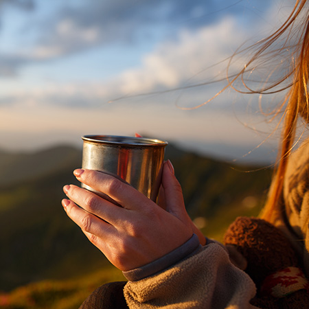 woman drinking a hot drink overlooking a mountain