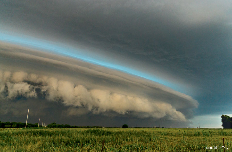 An arc of blue light reflects hail in the clouds of a massive storm cell sweeping across a Kansas plain