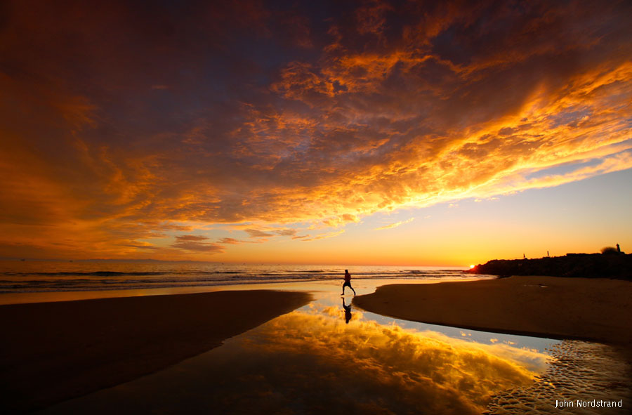 Man walking along beach at sunset