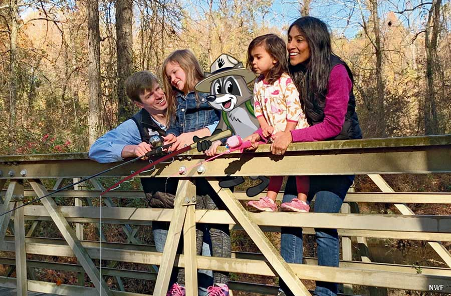 NWF CEO and President Collin O'Mara looks out over a bridge with a woman, children and Ranger Rick