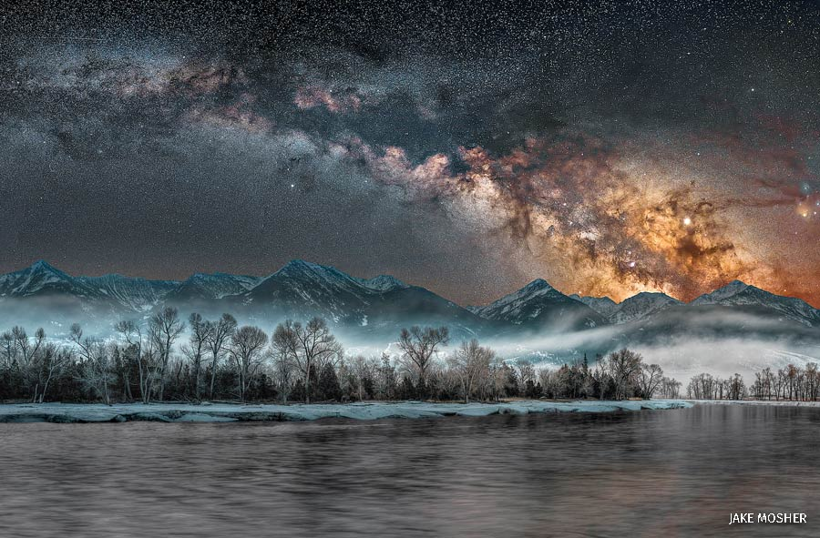 A landscape of the Yellowstone River with mountains and the Milky Way in the background.