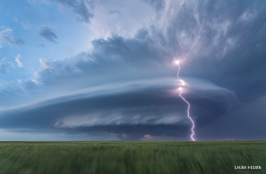 A strike of lighting comes out of a large storm cloud over the Great Plains.