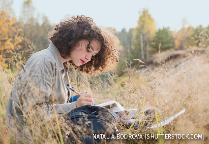 A young girl writing in a field
