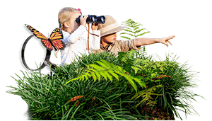 Two children in grass searching nature, one wearing a safari hat and pointing while the other one looks with binoculars.